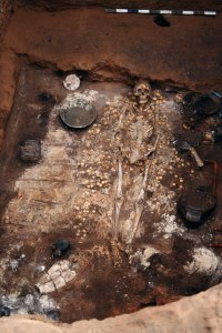 The burial chamber showing the body, and some of the grave goods. The mirror is visible to the middle right of the image, and the silver container on the top left.
